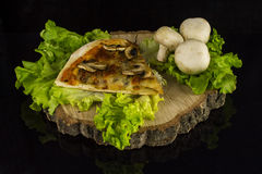 Pizza with mushrooms. Pizza piece with mushrooms dekorated with lettuce and mushrooms on a stump on a black background with reflection Stock Images