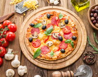 Pizza with mushrooms, salami and tomatoes. Stock Photos