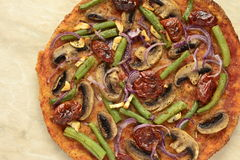 Pizza with mushrooms, sun-dried tomatoes, green beans and onions Royalty Free Stock Image