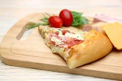 Pizza n ein Schneidebrett Stockfotografie