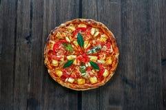 Pizza na ciemnym drewno stole, odgórny widok Zdjęcia Stock
