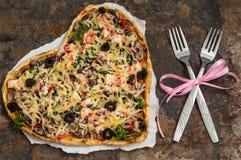 Pizza na forma de um coração Jantar romântico Tabela velha Vista superior Close-up fotos de stock royalty free