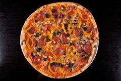Pizza na tabela de madeira preta. Trajeto de grampeamento incluído. Imagem de Stock Royalty Free