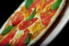 Pizza no fundo preto Fotografia de Stock Royalty Free