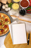 Pizza kitchen cooking, recipe book, ingredients, copy space. Freshly baked pepperoni Pizza with blank notebook or cookbook, chopping board and various Stock Images