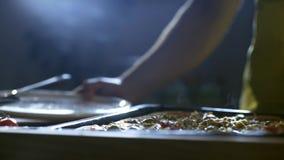 Pizza nova do corte do cozinheiro chefe nas partes 4K vídeos de arquivo