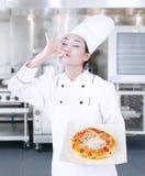 Läcker pizzahåll vid kock på kök Royaltyfria Foton