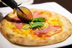 Pizza och pizzaskärare fotografering för bildbyråer