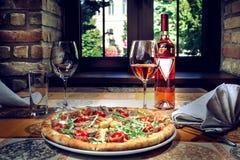 Pizza och rött vin på tabellen arkivfoto
