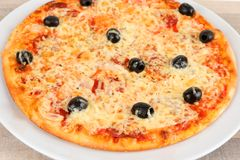 A pizza with olives and salami stock photo