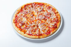 Pizza with onion, ham, cheese and tomato. White background Royalty Free Stock Image