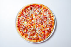 Pizza with onion, ham, cheese and tomato. White background Stock Photo