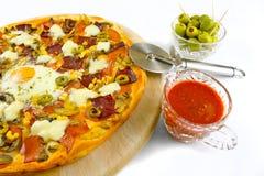 Pizza op houten plaat met chroomsnijder Stock Fotografie