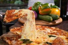 Pizza opheffende plak op houten raad Stock Fotografie