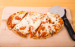 Pizza oval cortada en el tablero de madera Fotos de archivo libres de regalías