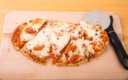 Pizza oval cortada na placa de madeira Fotos de Stock Royalty Free