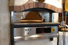 The pizza oven in the city cafe is ready for work stock image
