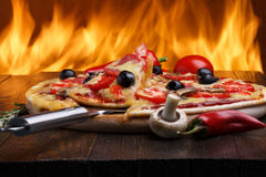 Pizza with oven fire on background Royalty Free Stock Image
