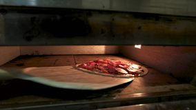 Pizza in the oven. Dough sausages and vegetables stock video footage