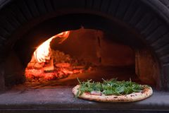 Pizza oven with rucola. Pizza in the oven ready to eat with rucola and raw ham Royalty Free Stock Photos