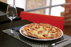 Pizza over table. A pizza served at restaurant table Stock Images