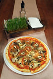 Pizza på en trätabell royaltyfri foto