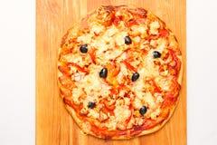 Pizza på ett träbräde Fotografering för Bildbyråer