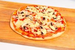 Pizza på ett träbräde Arkivfoton