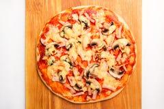 Pizza på ett träbräde Royaltyfri Bild