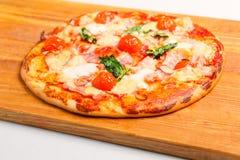 Pizza på ett träbräde Arkivbild