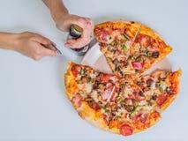 Pizza på tabellen med flickahanden Arkivfoto