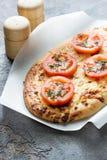 Pizza, pan con queso y tomates rojos, especias verdes Imagen de archivo