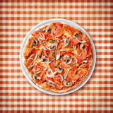 Pizza with paprika and mushrooms on old picnic tablecloth Stock Image