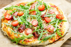 Pizza with parma ham. On old wooden table royalty free stock image