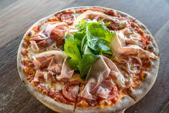 Pizza parma ham. And rocket salad on wooden table royalty free stock photography