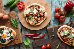 Pizza party flatlay. Freshly backed homemade rustic pizzas with royalty free stock image