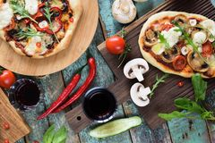 Pizza party flatlay. Rustic pizzas with bell pepper, mushrooms a royalty free stock photography