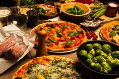 Pizza, pasta and vegetables. A delicious pizza on a wooden table served on a plate with garlic in foreground. Olive oil, salt, spices and vinegar in background royalty free stock photos