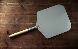 Pizza peel paddle italian style with wood handle on wooden table royalty free stock photo