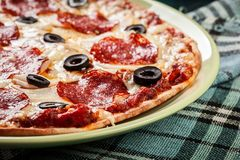 Pizza pepperoni with olives served Stock Images