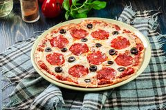 Pizza pepperoni with olives served Stock Photo