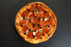 Pizza with pepperoni sausage and olives top view Royalty Free Stock Photos