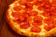 Pizza Pepperoni with sausages. Over wooden bacground royalty free stock image