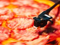 Pizza pepperoni spinning on turntable vinyl player. Concept of party, delicious junk food. Italian pizza with salami stock photography