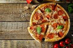 Pizza with pepperoni, tomato sauce and cheese royalty free stock photo