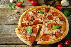 Pizza with pepperoni, tomato sauce and cheese stock images