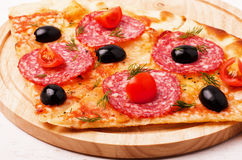 Pizza with pepperoni, tomatoes and olives Stock Photo