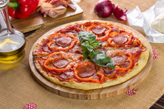 Pizza Pepperoni on the wooden plate. Pizza Pepperoni garnished with basil, bacon, mushrooms, pepper, ham, onion and oil Royalty Free Stock Photo