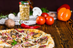 Pizza with pickles on wooden table, tomatoes and other vegetable Stock Images
