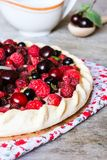 Pizza pie with mascarpone cream cheese, raspberry, black currant, strawberry, cherry on a wooden table. Homemade pie. Fruit pizza. royalty free stock photo
